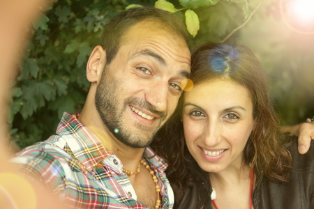 Couple of persons doing selfie in a park Stock Photo