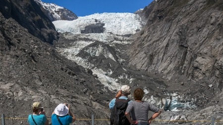 tourists take photographs of franz josef glacier on the weest coast of new zealand