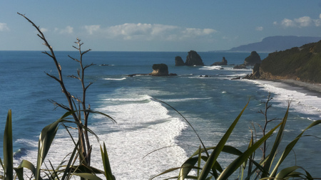surf rolls in at nine mile, near greymouth, on the west coast of new zealands south island