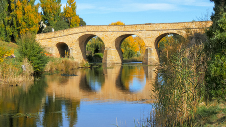 reflections of historic old stone bridge in the waters of the coal river at richmond, tasmania
