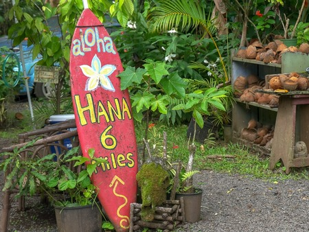 an old surfboard at a roadside stand on the road to hana