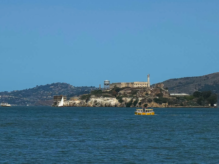 a cute small yellow ferry sails past alcatraz island in san francisco