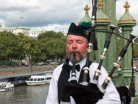 LONDON, ENGLAND, UK - SEPTEMBER 17, 2015: a bagpipes payer performs on a bridge over the river thames in london