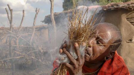 Ein Massai-Krieger zündet auf traditionelle Weise bei einer Manyatta in Kenia das Feuer an Standard-Bild