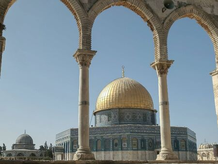 dome of the rock mosque framed by arches in jerusalem