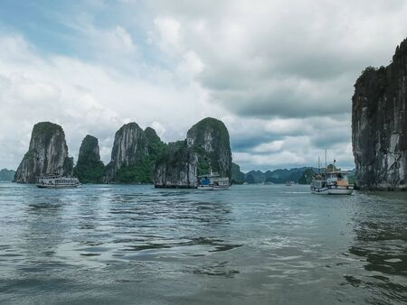 morning shot of a tour boat flotilla sailing in halong bay