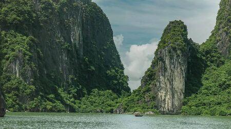 long shot of a vietnamese fishing boat at halong bay