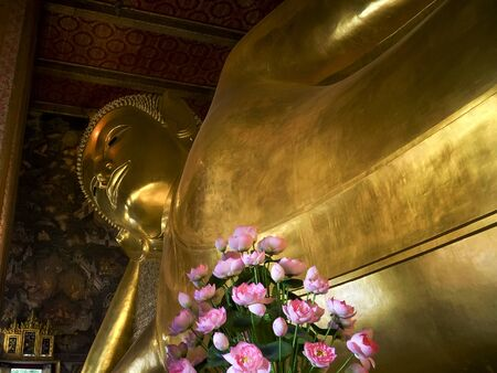 wide view of the reclining buddha with flowers in the foreground, bangkok