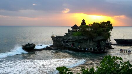 tourists wading out to tanah lot temple at sunset Reklamní fotografie