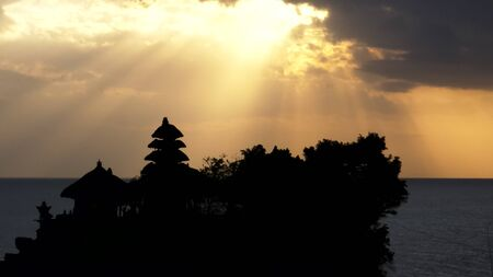 sun rays above a silhouetted tanah lot temple on bali