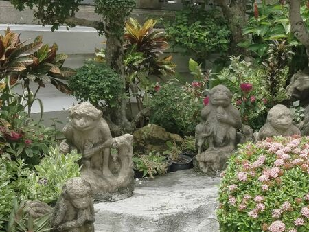 monkey statues in the gardens of the emerald buddha temple in bangkok