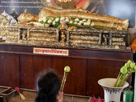 woman with lotus kneels before a buddha at golden mount in bangkok