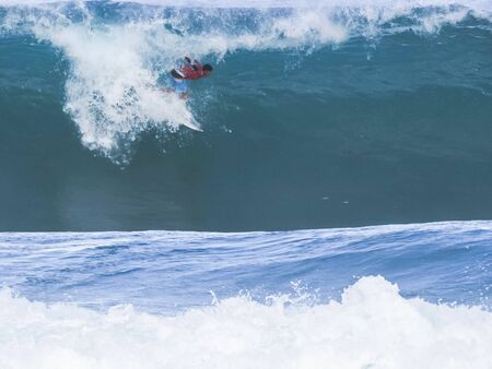 surfer getting a tube ride at pipeline, hawaii