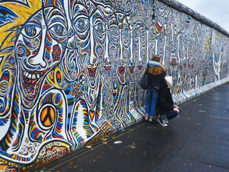 BERLIN, GERMANY OCTOBER, 6, 2017: tourists posing beside the berlin wall in germany 新聞圖片