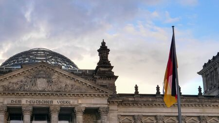 reichstag dome and german national flag at berlin in germany Stok Fotoğraf