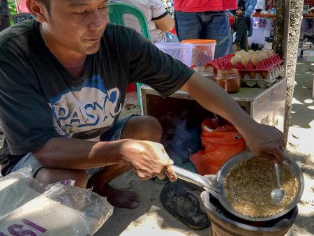 KUTA, INDONESIA - MARCH, 18, 2018: food vendor prepares kerak telor on a street at kuta beach in bali