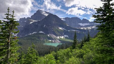 grinnell lake pine framed by pine trees at glacier national park
