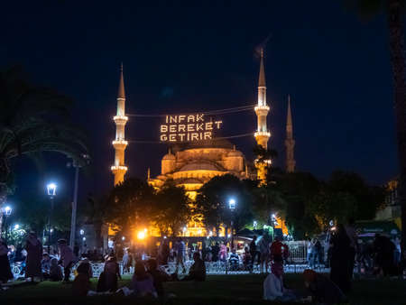 night shot of the blue mosque exterior in istanbul, turkey- mahya says infak bereket getirir in english it means help is bringing blessing . Archivio Fotografico
