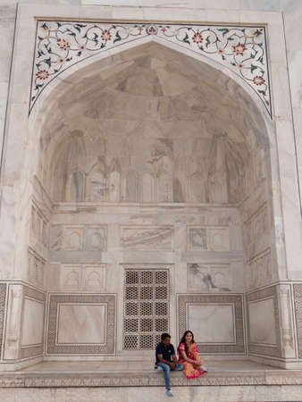 AGRA, INDIA - MARCH, 26, 2019: an indian couple rest in front of the taj mahal