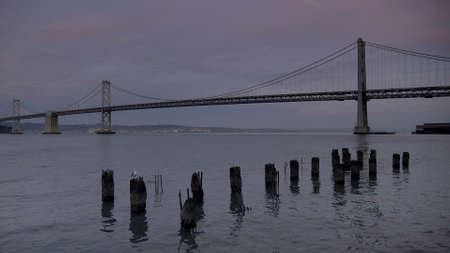 sunset shot of old pylons and the bay bridge in san francisco