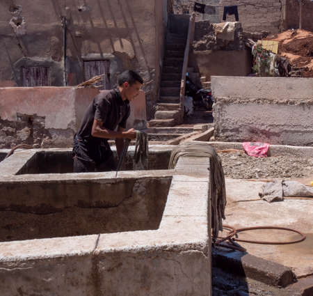 MARRAKESH, MOROCCO- JUNE, 10, 2019: tannery worker at one of the ancient tanneries