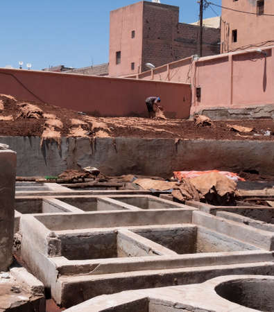 MARRAKESH, MOROCCO- JUNE, 10, 2019: worker and vats for tanning leather at one of the ancient tanneries in marrakesh