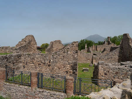 NAPLES, ITALY- JUNE, 13, 2019: wide shot of several house ruins at pompeii with mt vesuvius in the distance