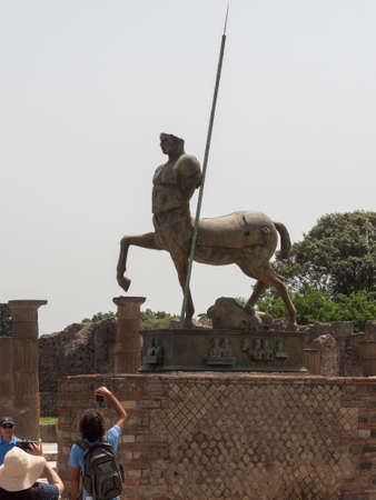 NAPLES, ITALY- JUNE, 13, 2019: modern art bronze statue of a centaur at the ruins of pompeii 新闻类图片