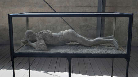 NAPLES, ITALY- JUNE, 13, 2019: a plaster cast of a woman victim in a glass case at pompeii 新闻类图片