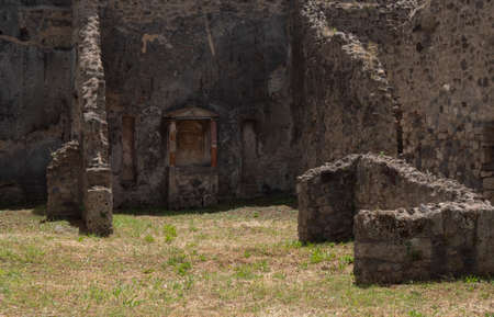 NAPLES, ITALY- JUNE, 13, 2019: the ruins of a house in the ancient roman city of pompeii with its family shrine