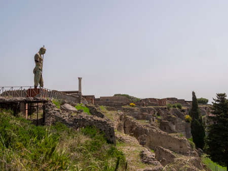NAPLES, ITALY- JUNE, 13, 2019: ruined buildings and a modern art bronze statue of a soldier with a spear at pompeii ruins