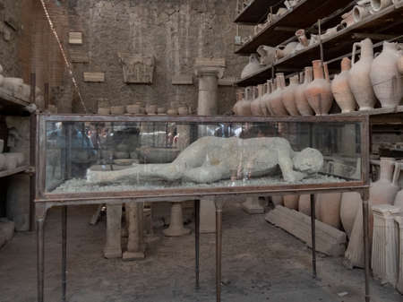 NAPLES, ITALY- JUNE, 13, 2019: plaster cast of a victim, in a glass case, at pompeii ruins