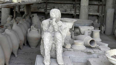 NAPLES, ITALY- JUNE, 13, 2019: plaster cast of a victim in a sitting position at pompeii