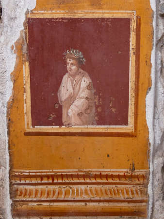 NAPLES, ITALY- JUNE, 13, 2019: fresco of a figure wrapped in a toga and wearing a laurel crown, in the House of the vettii, one of the houses in pompeii
