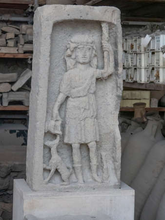 NAPLES, ITALY- JUNE, 13, 2019: a stone carving of a child and yheir pet dog at pompeii