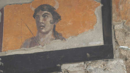 NAPLES, ITALY- JUNE, 13, 2019: a fresco of a woman on a house wall at pompeii 新闻类图片