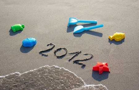 2012 hand-written on the sand of the beach with toys photo