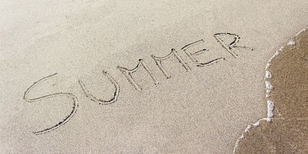 Summer hand-written on the sand of the beach photo