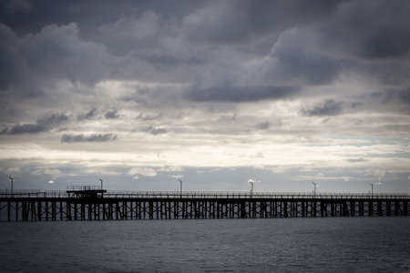 looming: Long jettypier with looming clouds overhead