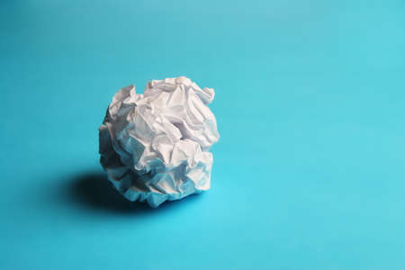 useless: Scrunched paper on a blue background Stock Photo