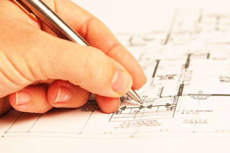 hand holding a pen, drawing building plans