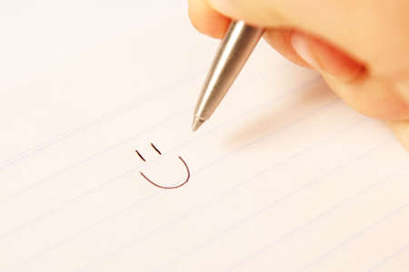Hand writing a smiley face on paper