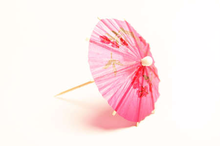 Pink cocktail umbrella on white