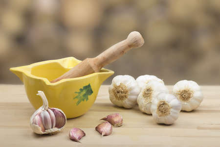 Garlic on chopping wood and container natural background photo