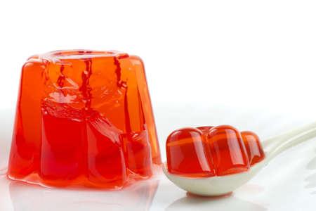gelatina: Red postre de gelatina con una cuchara sobre fondo blanco Foto de archivo