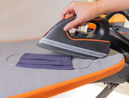 A woman is ironing a washable face mask