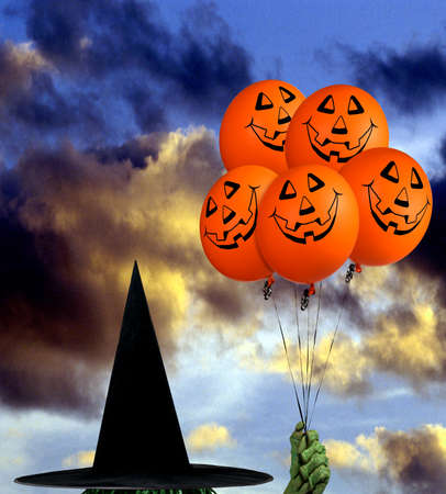Balloons with a Halloween Smiley and a cloudy evening Sky in the Background