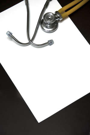 A blank paper with a stethoscope and a pen on a desk photo