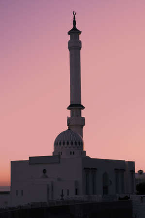 A pink sunset sky surrounding the Mosque photo