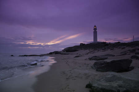 A tranquil beach with a purple sunset with a lighthouse in the background photo